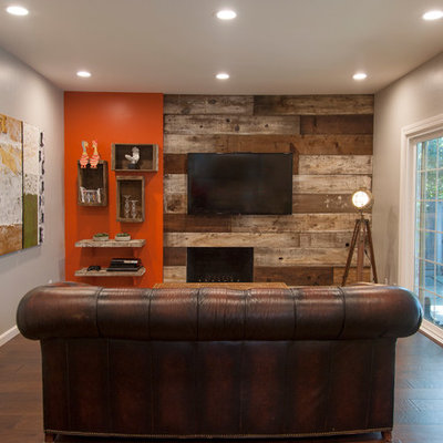 Inspiration for a mid-sized rustic enclosed dark wood floor living room remodel in San Francisco with orange walls, a standard fireplace and a wood fireplace surround