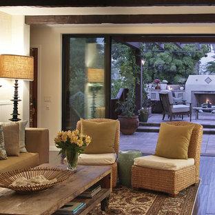 Esempio di un grande soggiorno mediterraneo aperto con pareti beige, pavimento in linoleum, camino classico, cornice del camino in intonaco e pavimento marrone