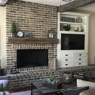 Idee per un soggiorno country di medie dimensioni con pareti beige, pavimento in legno massello medio, camino classico, cornice del camino in mattoni, parete attrezzata e pavimento marrone