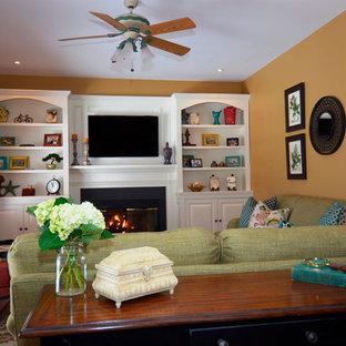 Modelo de salón para visitas abierto, tradicional, de tamaño medio, con parades naranjas, suelo de madera oscura, chimenea tradicional, marco de chimenea de yeso y televisor colgado en la pared