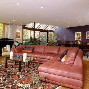 Idee per un soggiorno contemporaneo aperto con sala della musica, pavimento in legno massello medio e pareti viola