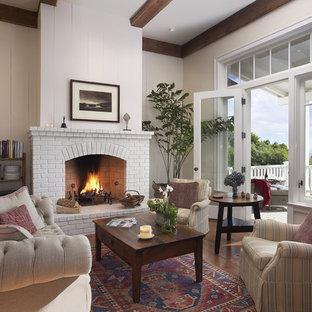 Immagine di un soggiorno chic di medie dimensioni con camino classico e cornice del camino in mattoni