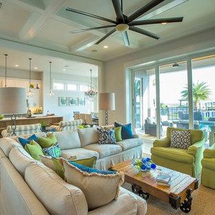ジャクソンビルの大きいビーチスタイルのおしゃれなLDK (白い壁、淡色無垢フローリング、標準型暖炉、壁掛け型テレビ、レンガの暖炉まわり) の写真