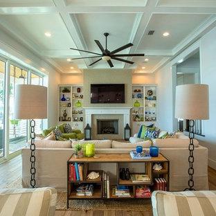 ジャクソンビルの大きいビーチスタイルのおしゃれなLDK (白い壁、淡色無垢フローリング、標準型暖炉、レンガの暖炉まわり、壁掛け型テレビ) の写真