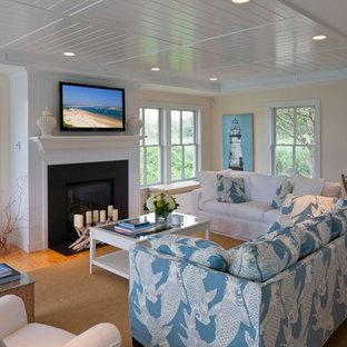 Imagen de salón abierto, marinero, de tamaño medio, con chimenea tradicional, televisor colgado en la pared, paredes beige, suelo de madera clara, marco de chimenea de metal y suelo marrón