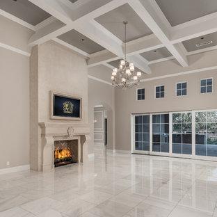 フェニックスの巨大なモダンスタイルのおしゃれなリビング (ベージュの壁、大理石の床、標準型暖炉、石材の暖炉まわり、壁掛け型テレビ、マルチカラーの床) の写真