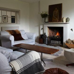 ドーセットの中サイズのビーチスタイルのおしゃれな独立型リビング (白い壁、塗装フローリング、標準型暖炉、木材の暖炉まわり) の写真