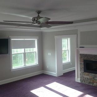Modelo de salón abierto, campestre, grande, con paredes grises, moqueta, chimenea lineal, marco de chimenea de piedra, televisor colgado en la pared y suelo violeta