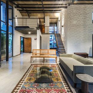 Idee per un soggiorno tropicale aperto con pareti beige, pavimento in cemento e TV autoportante