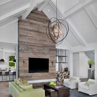 Modelo de salón abierto, tradicional renovado, con paredes blancas, suelo de madera clara y pared multimedia