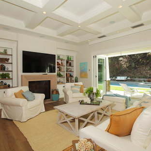 Design ideas for a large country open concept living room in Los Angeles with beige walls, medium hardwood floors, a standard fireplace, a plaster fireplace surround and a wall-mounted tv.