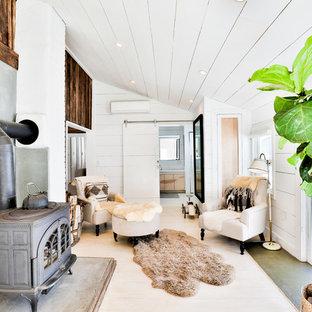 Diseño de salón para visitas cerrado, de estilo de casa de campo, sin televisor, con paredes blancas, suelo de madera clara, estufa de leña, suelo beige y marco de chimenea de hormigón