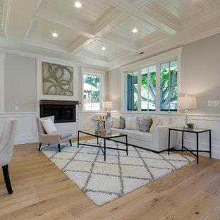 サンフランシスコの中くらいのカントリー風おしゃれなリビング (グレーの壁、淡色無垢フローリング、横長型暖炉、木材の暖炉まわり、壁掛け型テレビ、ベージュの床) の写真
