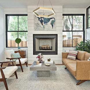 Repräsentatives, Fernseherloses Landhaus Wohnzimmer mit weißer Wandfarbe, hellem Holzboden, Kamin, Kaminumrandung aus Holz und braunem Boden in Austin