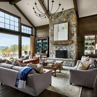 Idée de décoration pour un salon champêtre avec un mur blanc, un sol en bois foncé, une cheminée standard, un manteau de cheminée en pierre et un sol marron.