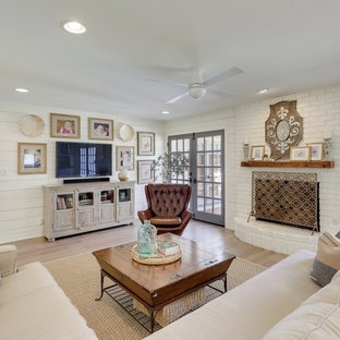 Inspiration for a medium sized rural formal enclosed living room in Austin with light hardwood flooring, white walls, a standard fireplace, a brick fireplace surround, a wall mounted tv and beige floors.