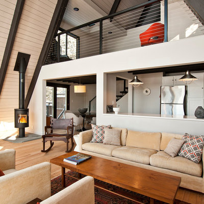 Inspiration for a mid-sized country formal and open concept light wood floor and beige floor living room remodel in New York with white walls, a wood stove and no tv