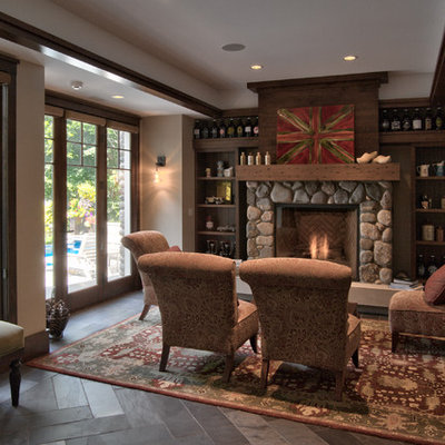 Example of a mid-sized farmhouse open concept slate floor and gray floor living room design in Minneapolis with beige walls, a standard fireplace, a stone fireplace and no tv