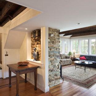 ワシントンD.C.の大きいトラディショナルスタイルのおしゃれなLDK (茶色い壁、無垢フローリング、標準型暖炉、石材の暖炉まわり、テレビなし、ベージュの床) の写真