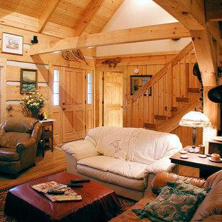 Diseño de salón abierto, rural, pequeño, sin televisor, con suelo de madera en tonos medios, chimenea tradicional y marco de chimenea de piedra