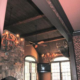 Diseño de salón cerrado, rústico, de tamaño medio, con paredes marrones, chimenea tradicional y marco de chimenea de piedra