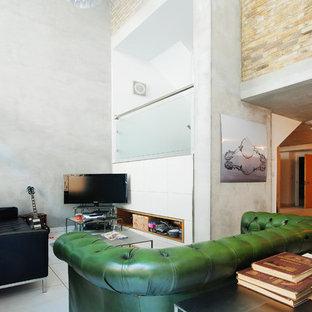 グロスタシャーの巨大なインダストリアルスタイルのおしゃれなリビングロフト (ミュージックルーム、グレーの壁、コンクリートの床、据え置き型テレビ) の写真