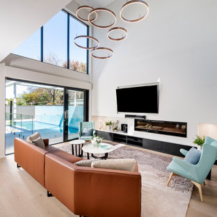 Design ideas for an expansive contemporary open concept living room in Perth with white walls, medium hardwood floors, a ribbon fireplace, a wall-mounted tv and beige floor.
