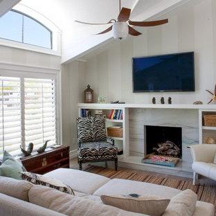 サンディエゴの中サイズのビーチスタイルのおしゃれなLDK (マルチカラーの壁、淡色無垢フローリング、標準型暖炉、石材の暖炉まわり、壁掛け型テレビ、フォーマル、茶色い床) の写真