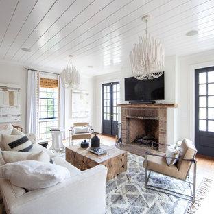 Idee per un soggiorno country chiuso con pareti bianche, pavimento in legno massello medio, camino classico, cornice del camino in mattoni, TV a parete e pavimento marrone