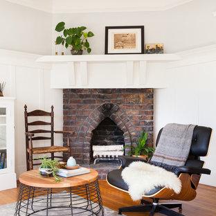 Idéer för ett klassiskt vardagsrum, med grå väggar, mellanmörkt trägolv, en öppen hörnspis och en spiselkrans i tegelsten