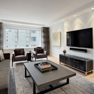 This is an example of a medium sized contemporary enclosed living room in New York with white walls, light hardwood flooring, no fireplace and a wall mounted tv.