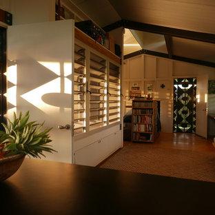 Esempio di un piccolo soggiorno tropicale aperto con pareti bianche e pavimento in compensato