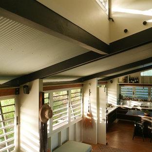 Ispirazione per un piccolo soggiorno tropicale aperto con pareti bianche e pavimento in compensato