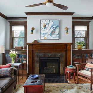 Immagine di un soggiorno stile americano chiuso con libreria, pareti grigie, parquet chiaro, camino classico, cornice del camino piastrellata e nessuna TV