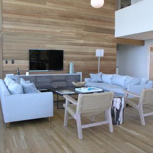 Modelo de salón abierto, actual, grande, con televisor colgado en la pared, paredes marrones, suelo de madera clara, chimenea tradicional y marco de chimenea de piedra