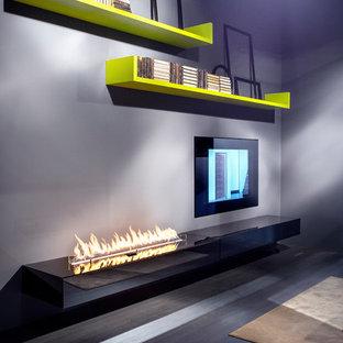 Esempio di un grande soggiorno minimalista aperto con pareti nere, pavimento in cemento, camino bifacciale e nessuna TV