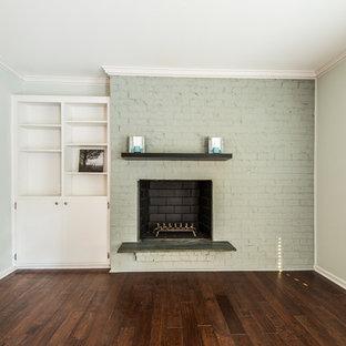 Esempio di un soggiorno stile americano con pareti verdi, pavimento in legno massello medio, camino classico, cornice del camino in mattoni e pavimento marrone