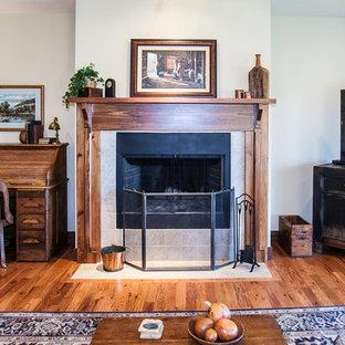 Foto di un soggiorno stile americano di medie dimensioni e aperto con pareti beige, pavimento in legno massello medio, stufa a legna, cornice del camino in legno e TV autoportante