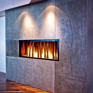 ポートランドのアジアンスタイルのおしゃれなリビング (コンクリートの暖炉まわり) の写真