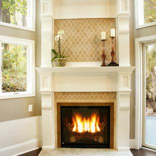 ニューヨークの大きいトラディショナルスタイルのおしゃれなLDK (フォーマル、ベージュの壁、磁器タイルの床、吊り下げ式暖炉、漆喰の暖炉まわり、テレビなし、茶色い床) の写真