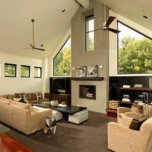 ワシントンD.C.の中サイズのコンテンポラリースタイルのおしゃれなLDK (据え置き型テレビ、フォーマル、ベージュの壁、無垢フローリング、標準型暖炉、漆喰の暖炉まわり、茶色い床) の写真