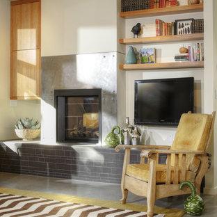 Modelo de biblioteca en casa abierta, moderna, de tamaño medio, con suelo de cemento, paredes blancas, chimenea tradicional, marco de chimenea de metal, televisor colgado en la pared y suelo gris