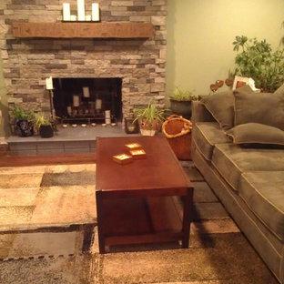 Foto di un soggiorno chic di medie dimensioni e chiuso con pareti verdi, pavimento in legno massello medio, camino classico, cornice del camino in pietra e nessuna TV