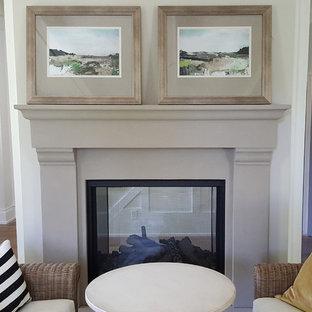 Foto di un soggiorno chic con pareti bianche, pavimento in legno massello medio, camino classico e cornice del camino in intonaco