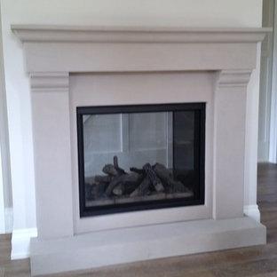 他の地域のトラディショナルスタイルのおしゃれなリビング (白い壁、無垢フローリング、標準型暖炉、漆喰の暖炉まわり) の写真