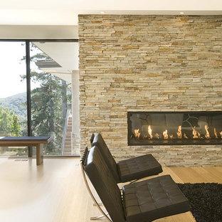 Foto di un soggiorno minimalista con camino lineare Ribbon, cornice del camino in pietra e pavimento in bambù