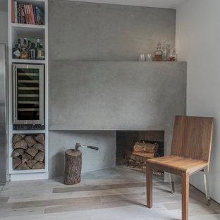 Foto di un piccolo soggiorno nordico chiuso con pareti bianche, parquet chiaro, camino ad angolo, cornice del camino in cemento, nessuna TV e pavimento beige