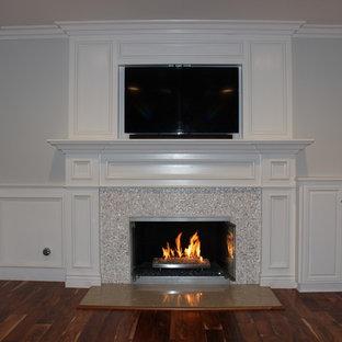 Idéer för mellanstora funkis separata vardagsrum, med ett finrum, beige väggar, mellanmörkt trägolv, en standard öppen spis, en spiselkrans i trä och en inbyggd mediavägg