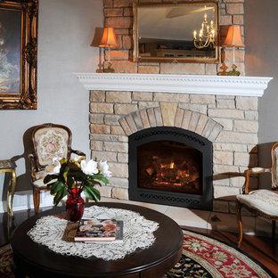 クリーブランドの中くらいのトラディショナルスタイルのおしゃれな独立型リビング (フォーマル、グレーの壁、濃色無垢フローリング、コーナー設置型暖炉、石材の暖炉まわり、テレビなし、茶色い床) の写真