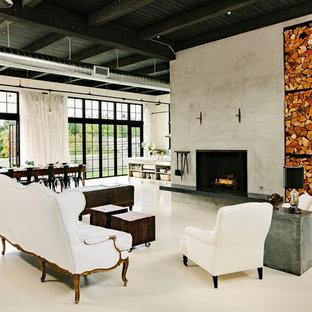 ポートランドのインダストリアルスタイルのおしゃれなリビング (コンクリートの暖炉まわり、白い床) の写真